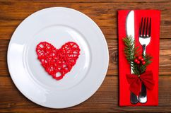 Christmas table: knife and fork, plate, napkin and Christmas tre. E branch on a wooden table top view with copy space. New Year& x27;s decor of the festive table Stock Photography