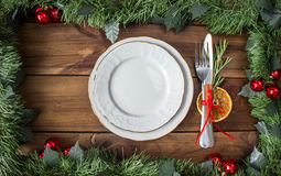 Christmas table layout, red tape with a cinnamon stick, rosmarin and a slice of dry orange. On the dark wooden background with christmas decorations Royalty Free Stock Photography