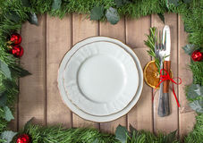 Christmas table layout, red tape with a cinnamon stick, rosmarin and a slice of dry orange. On the light wooden background with christmas decorations Royalty Free Stock Photos