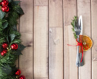Christmas table layout, red tape with a cinnamon stick, rosmarin and a slice of dry orange. On the light wooden background with christmas decorations Stock Photography