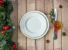 Christmas table layout, red tape with a cinnamon stick, rosmarin and a slice of dry orange. On the light wooden background with christmas decorations Stock Image