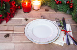 Christmas table layout, red tape with a cinnamon stick, rosmarin and a slice of dry orange. On the light wooden background with christmas decorations Royalty Free Stock Photography