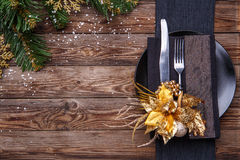 Christmas table place setting with black napkin, plate, fork and knife, decorated gold flower and christmas pine Royalty Free Stock Photography