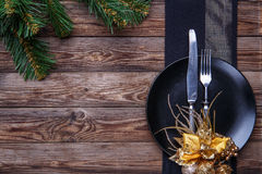 Christmas table place setting with black napkin, plate, fork and knife, decorated gold flower and christmas pine Stock Photos