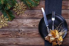 Christmas table place setting with black napkin, plate, fork and knife, decorated gold flower and christmas pine branches. Royalty Free Stock Image