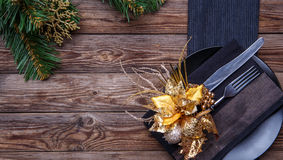 Christmas table place setting with black napkin, plate, fork and knife, decorated gold flower and christmas pine branches. Stock Photography