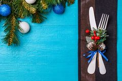 Christmas table place setting with black napkin, white fork and knife, decorated sprig of mistletoe and christmas pine. Branches. Christmas holidays background Stock Photography