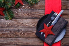 Christmas table place setting with black plate, fork and knife, decorated red star, black napkin and christmas pine Stock Photos