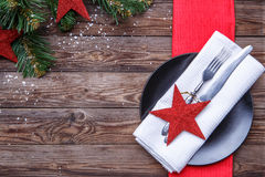 Christmas table place setting with black plate, fork and knife, decorated red star, white napkin and christmas pine Royalty Free Stock Image