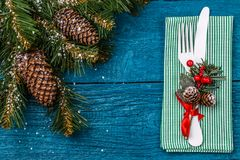 Christmas table place setting - blue table with green napkin, white fork and knife, decorated sprig of mistletoe and Stock Photo