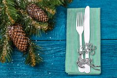 Christmas table place setting - blue table with green napkin, white fork and knife, decorated christmas tree toy - Royalty Free Stock Photos