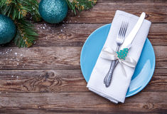 Christmas table place setting with blue plate, fork and knife, decorated ribbon and bow with fir-tree toy, white napkin Stock Photography