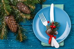 Christmas table place setting - blue table with green napkin, blue plate, white fork and knife, decorated sprig of Royalty Free Stock Photography