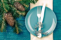Christmas table place setting - blue table with white napkin, blue plate, white fork and knife, decorated christmas tree Stock Images