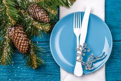 Christmas table place setting - blue table with white napkin, blue plate, white fork and knife, decorated christmas tree Royalty Free Stock Photo