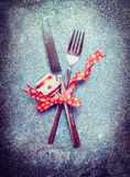 Christmas table place setting with cutlery and red decoration on dark rustic vintage background Royalty Free Stock Photo