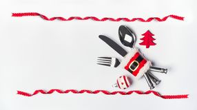 Christmas table place setting with cutlery, red ribbon frame and decoration , copy space on white desktop background, top view Stock Photo