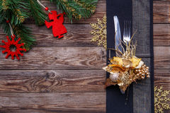 Christmas table place setting decorated black napkin with fork and knife, gold flower and snowflakes and christmas pine Stock Images