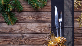 Christmas table place setting decorated black napkin with fork and knife, gold flower and snowflakes and christmas pine Stock Image