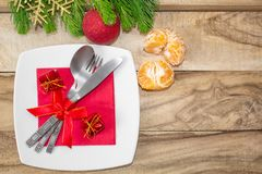 Christmas table place setting. Festive background. Branches of fir, balls, cutlery and tangerines. stock photo