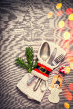 Christmas table place setting with festive decor, napkin, cutlery , handmade snowman and tag on gray background with bokeh Stock Photo
