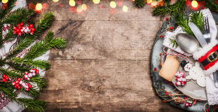 Christmas table place setting with festive decor, plate, cutlery , handmade snowman and blank tag on rustic wooden background, top. View, banner Royalty Free Stock Photos