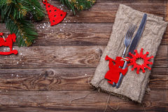 Christmas table place setting with fork and knife, decorated red christmas toys, sackcloth napkin and christmas pine branches. Stock Image