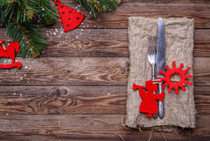 Christmas table place setting with fork and knife, decorated red christmas toys, sackcloth napkin and christmas pine branches. Stock Photo