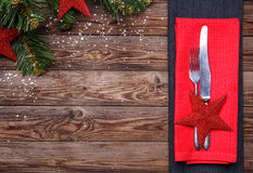 Christmas table place setting with fork and knife, decorated red star and red napkin, and christmas pine branches with Royalty Free Stock Photography