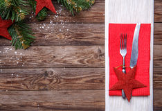 Christmas table place setting with fork and knife, decorated red star, red napkin and christmas pine branches with toys. Royalty Free Stock Photos