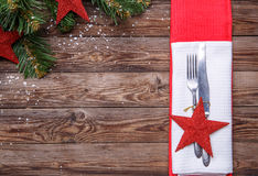 Christmas table place setting with fork and knife, decorated red star, white napkin and christmas pine branches with Stock Images