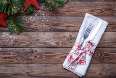 Christmas table place setting with fork and knife, decorated ribbon and bow, white napkin and christmas pine branches Stock Photography