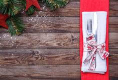 Christmas table place setting with fork and knife, decorated ribbon and bow, white napkin and christmas pine branches with toys. Stock Image