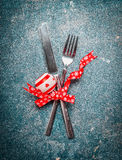 Christmas table place setting with fork, knife and red ribbon and decoration on vintage background Royalty Free Stock Photos