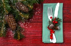 Christmas table place setting with green napkin, white fork and knife, decorated sprig of mistletoe and christmas pine. Branches. Christmas holidays background Royalty Free Stock Photos