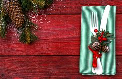 Christmas table place setting with green napkin, white fork and knife, decorated sprig of mistletoe and christmas pine. Branches. Christmas holidays background Stock Photos