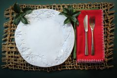 Christmas table place setting with handmade plate, red napkin and holly on rustic woven mat Royalty Free Stock Photo