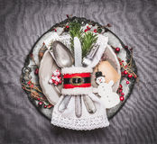 Christmas table place setting with holiday decor, plate, cutlery , handmade snowman and blank tag on gray background, top view. Christmas table place setting Stock Photo