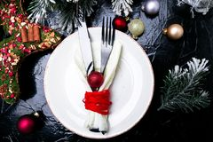 Christmas table place setting. Holidays background. White plate, knife and fork with christmas decorations on black table. Top vie Royalty Free Stock Images