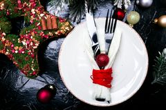 Christmas table place setting. Holidays background. White plate, knife and fork with christmas decorations on black table. Top vie Stock Photography