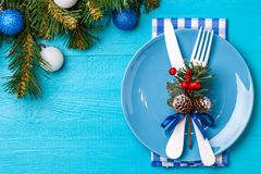 Christmas table place setting with napkin, blue plate, white fork and knife, decorated sprig of mistletoe and christmas. Pine branches. Christmas holidays Royalty Free Stock Photos