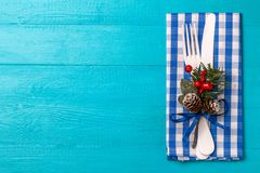 Christmas table place setting with napkin and white fork and knife, decorated sprig of mistletoe. Christmas holidays background Stock Images