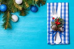 Christmas table place setting with napkin, white fork and knife, decorated sprig of mistletoe and christmas pine. Branches. Christmas holidays background Royalty Free Stock Image