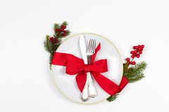 Christmas table place setting with plate, cutlery, pine branches,  ribbon and red berries. Winter holidays and festive background. Christmas eve dinner, New Stock Photos