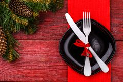 Christmas table place setting with red napkin, black plate, white fork and knife, decorated red bow and christmas pine. Branches. Christmas holidays background Stock Photography
