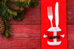 Christmas table place setting with red napkin, black plate, white fork and knife, decorated Santa jacket and christmas. Pine branches. Christmas holidays Stock Image