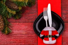 Christmas table place setting with red napkin, black plate, white fork and knife, decorated Santa jacket and christmas. Pine branches. Christmas holidays Royalty Free Stock Photo
