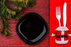 Christmas table place setting with red napkin, black plate, white fork and knife, decorated Santa jacket and christmas. Pine branches. Christmas holidays Royalty Free Stock Photography