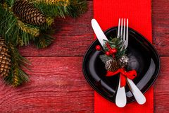 Christmas table place setting with red napkin, black plate, white fork and knife, decorated sprig of mistletoe and Royalty Free Stock Image