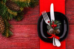 Christmas table place setting with red napkin, black plate, white fork and knife, decorated sprig of mistletoe and. Christmas pine branches. New Year Clock Stock Images